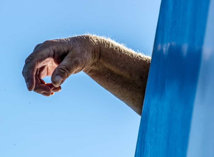 The arm of an elderly man overhanging a blue wall