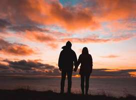 Silhouette photo of couple looking over sea at sunset