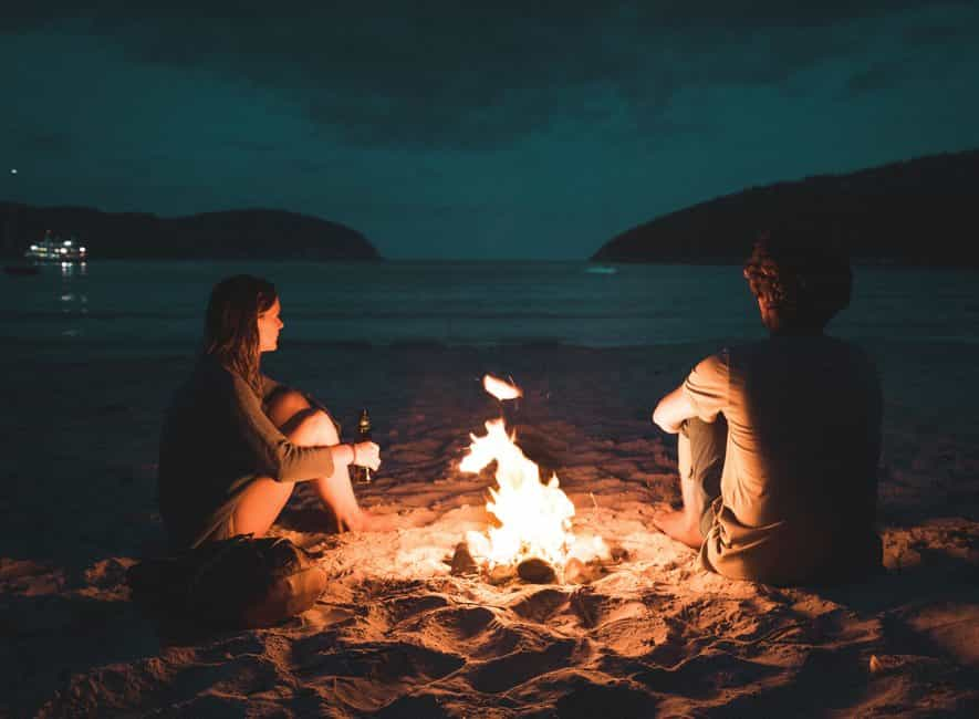 Couple sat next to small beach bonfire at night looking out to sea