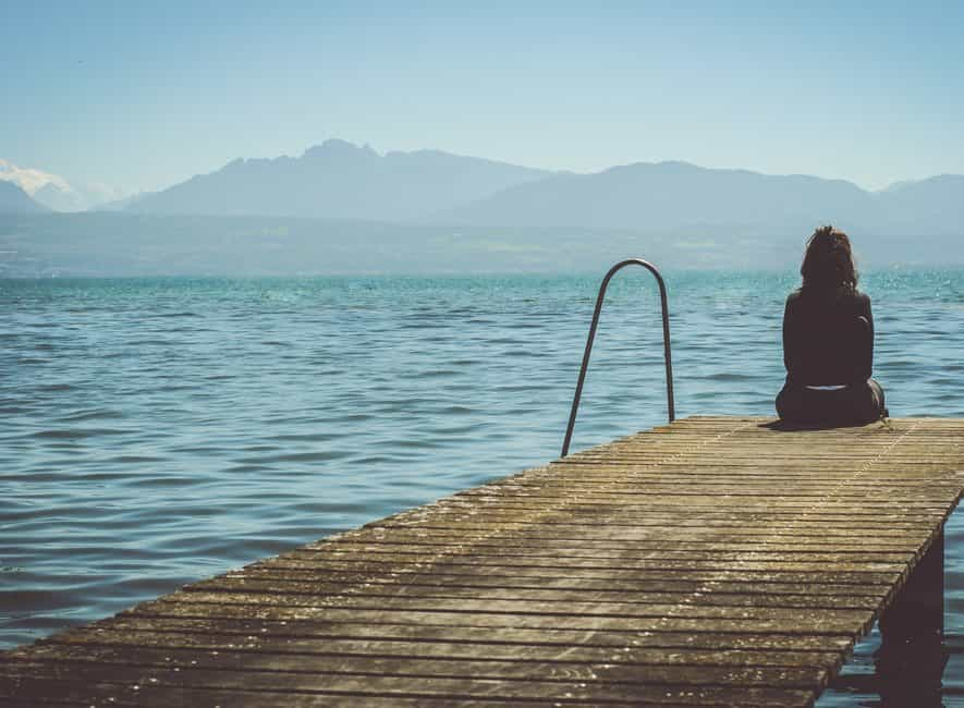 Woman sitting on dock looking out to sea during daytime
