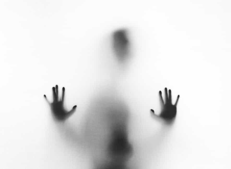 Person outline leaning against frosted glass with hands outstretched