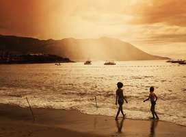 Two children playing on beach at sunset