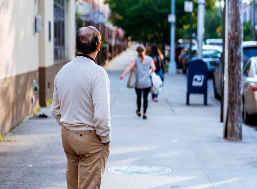 Man standing outside looking away from camera at another person leaving