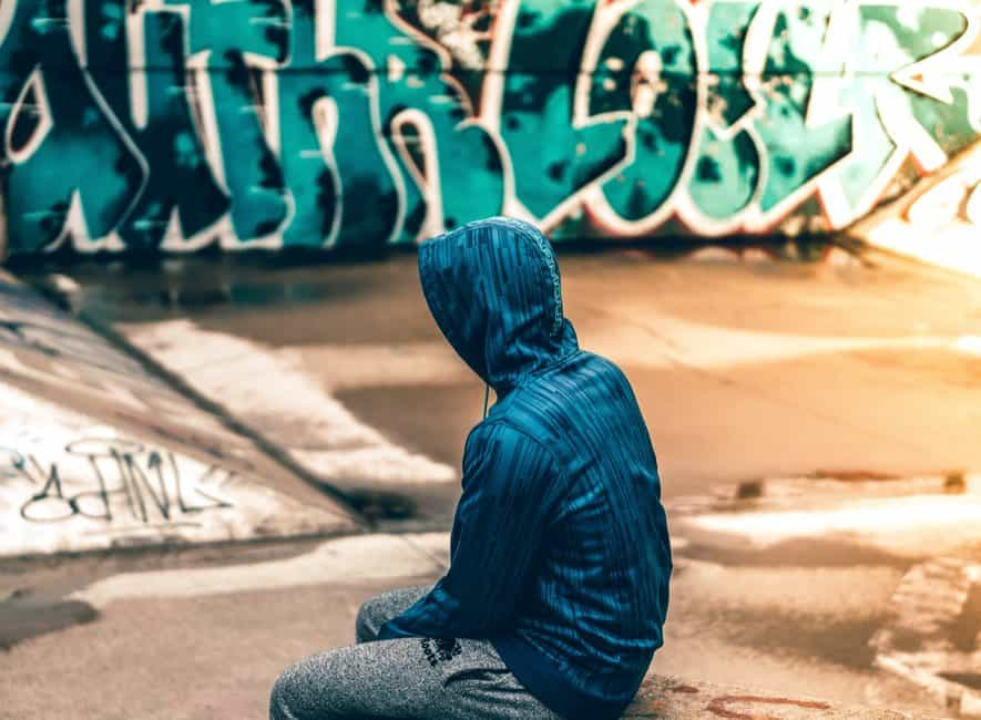 Person sitting near graffiti artwork wearning hoodie, face obscurred