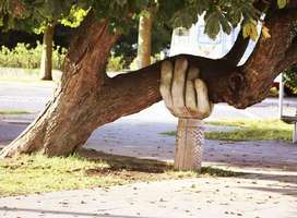 Brown tree leaning to one side supported by large wooden hand