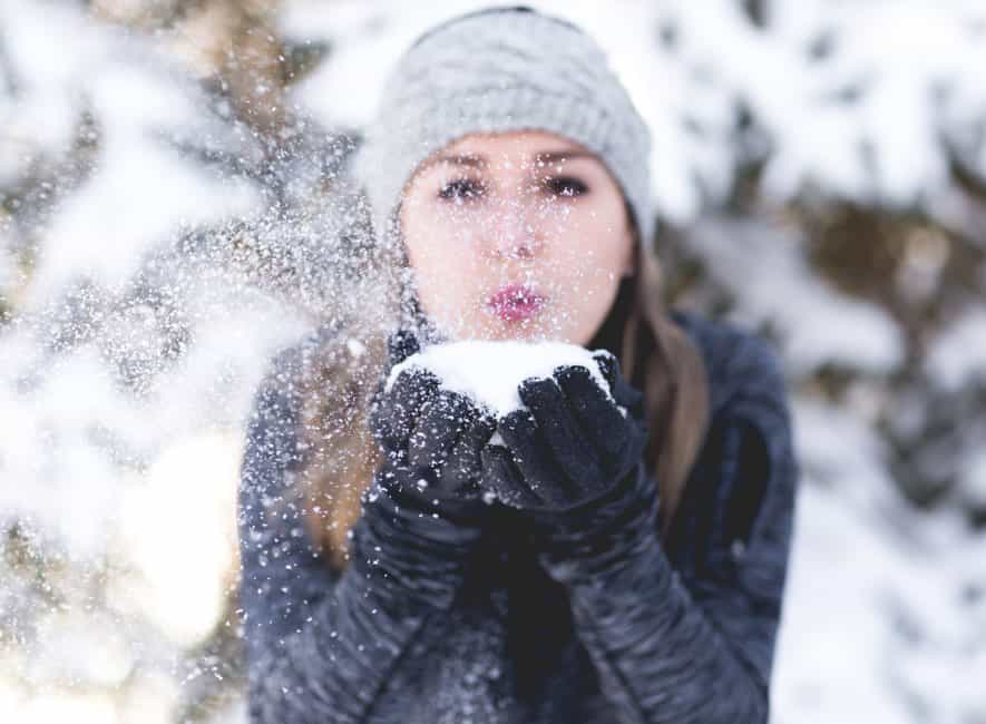 Young woman holding snowball and blowing snow cloud