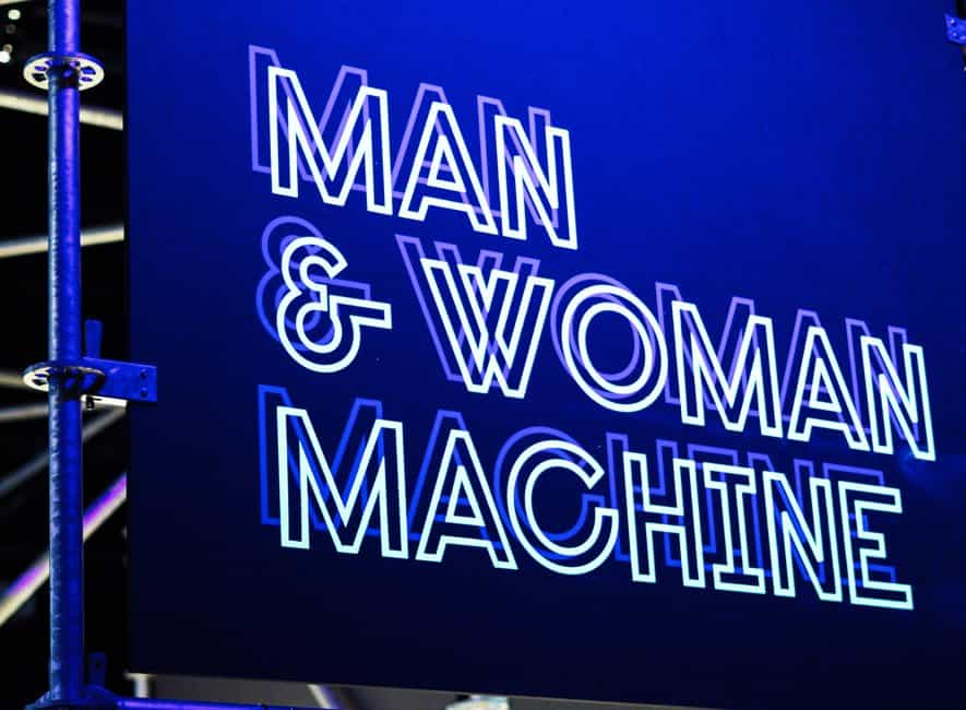 Illuminated neon sign with the words man and woman machine