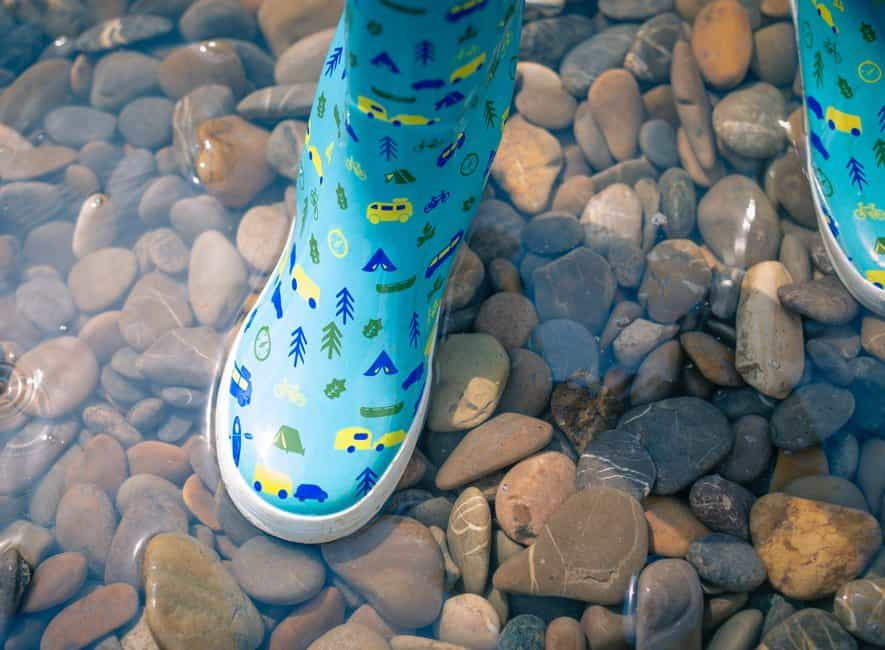 Child's waterproof boots standing in shallow water with pebbles