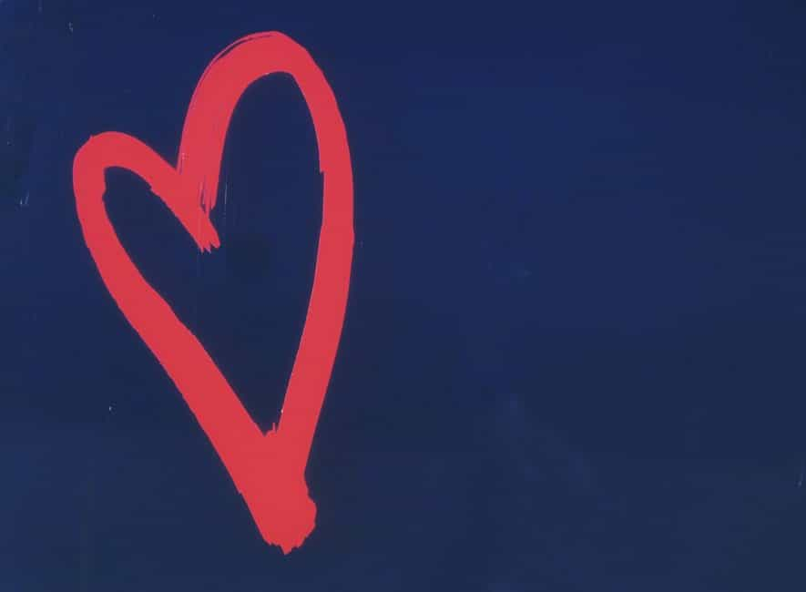 Painting of a red heart sign on blue background
