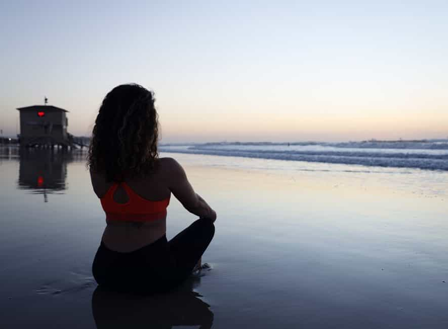 Woman sat on beach in early morning facing calm sea mediating