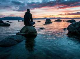 Young man sat on seashore rocks looking at calm sea and beautiful sunset