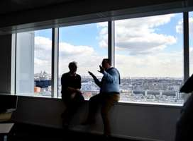 Two men sat on internal window ledge of large office window discussing