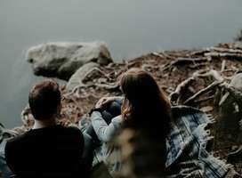 Young couple sat by lake side talking