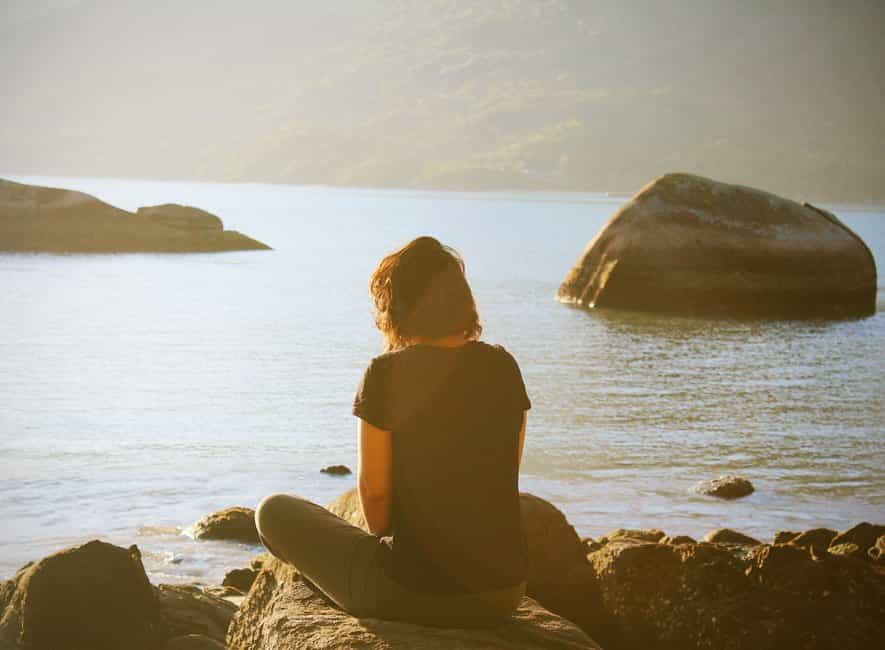 Woman sat on beach rocks in meditation pose facing out to calm sea