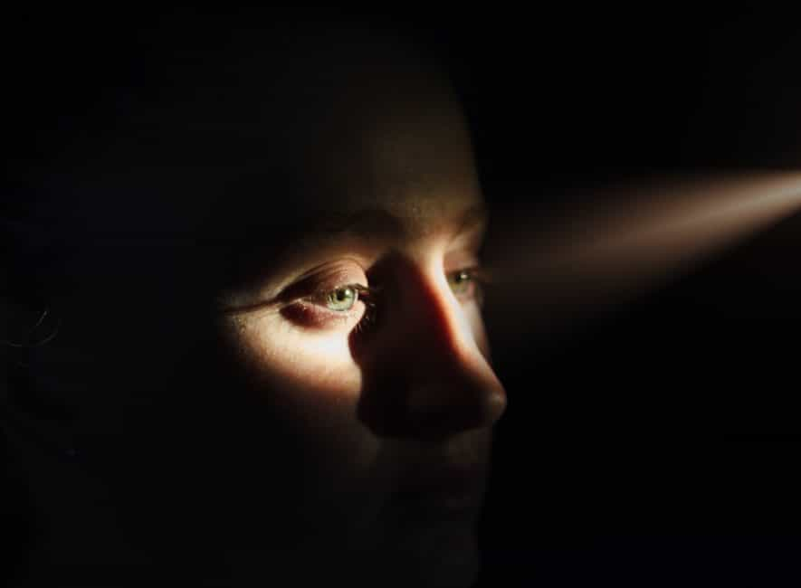 Woman's eyes looking sideways illuminated by shaft of sunlight rest of face in deep shadow