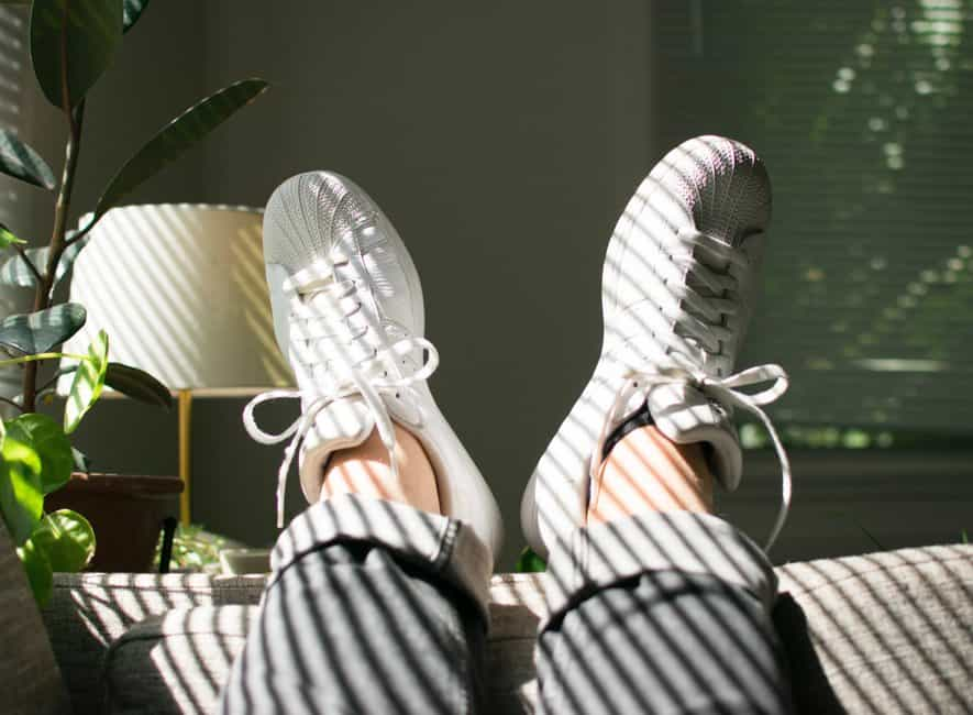 Feet with sneakers propped up on back of sofa