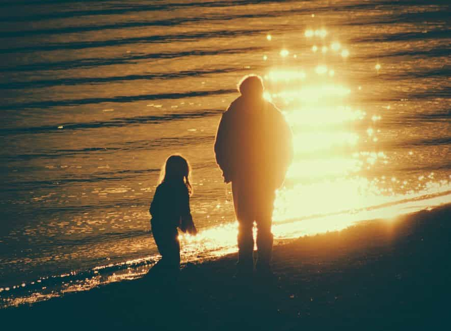 Family memories, adult and child near seashore during sunset