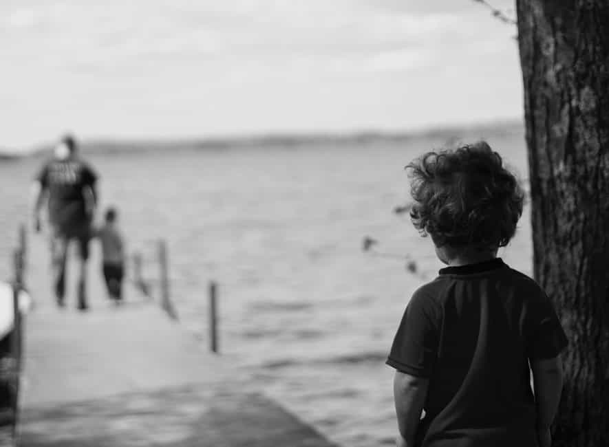 Monochrome photo of child looking out at dad walking towards him