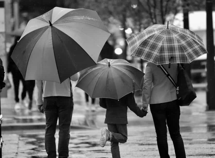 Grayscale photo of three person's holding umbrellas