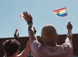 Two gay men waving multicolored flags in daytime