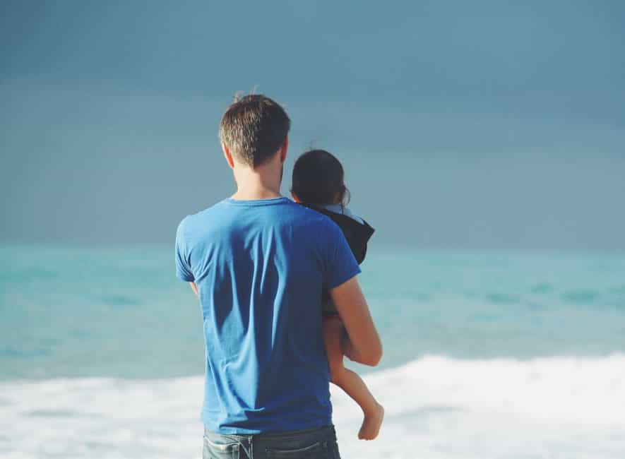 Back view of man holding child admiring beautiful blue sea and sky