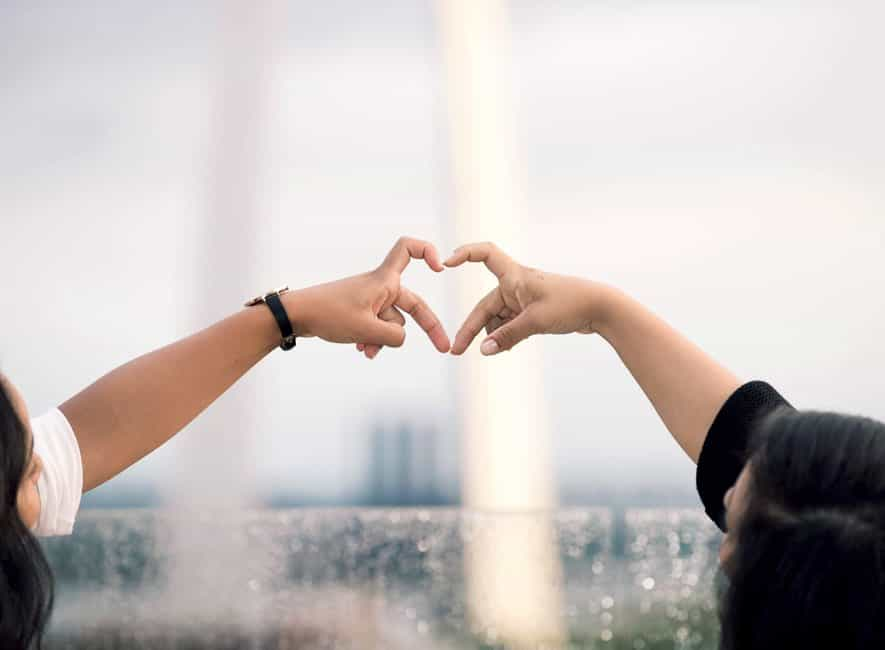 Two women doing heart hand sign during daytime
