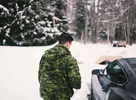 Soldier walking to car in the snow.