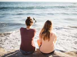 Two girl friends sat on shore rocks looking out to sea