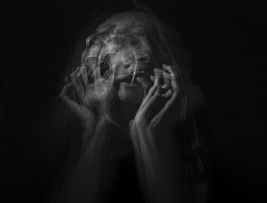 Monochrome time lapse photo of woman on black background screaming