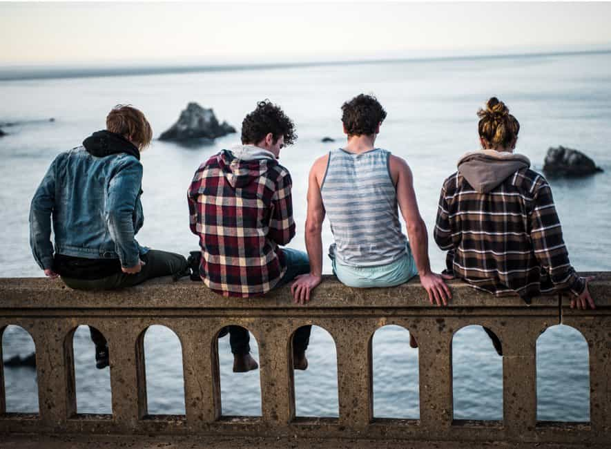 Four adolescent teens sitting on wall looking out to sea