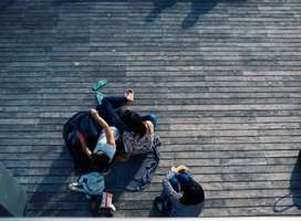 Aerial photo of three tens sitting on deck, faces obscurred