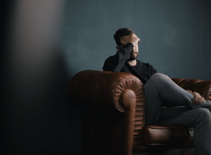 Man sitting on sofa against wall, with head in hand.