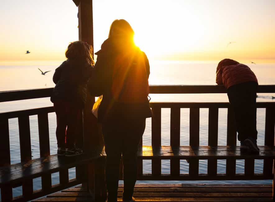 Photo of back view of female parent and two children looking over fence to sunset across sea