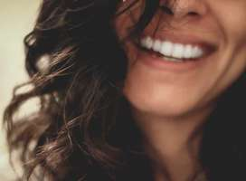Photo of smiling brown haired woman, eyes hidden