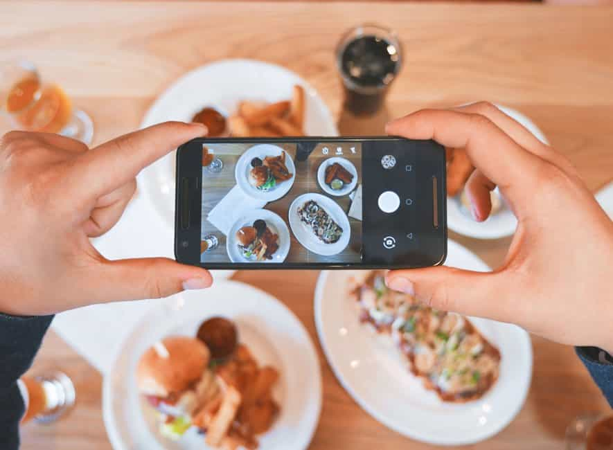 Person using smartphone to take a photo of prepared food on table