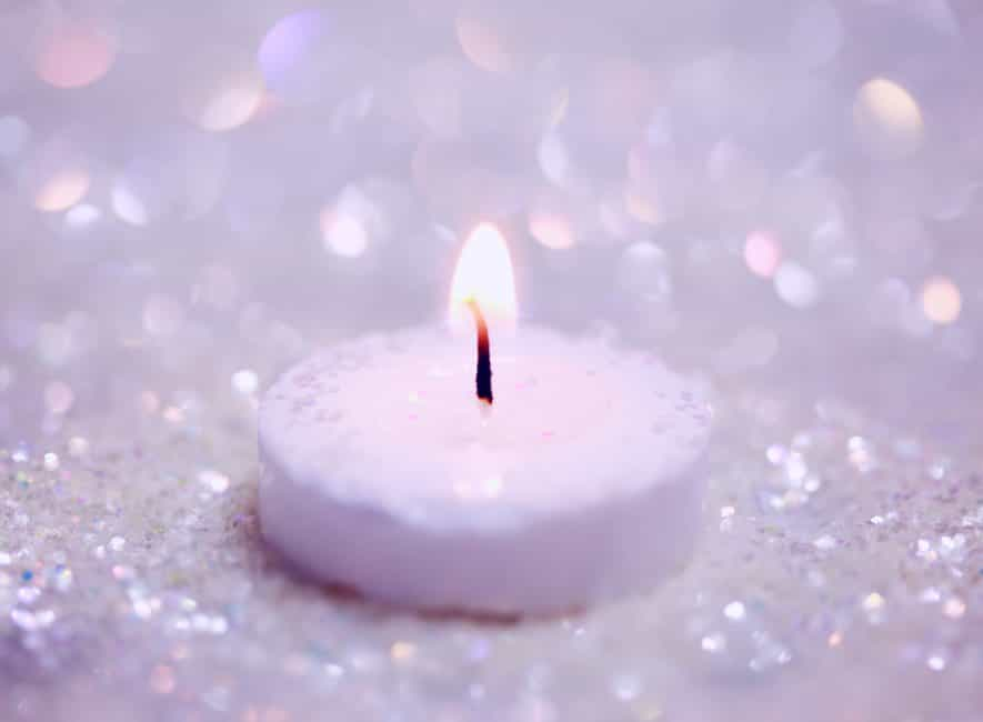 Illuminated white candle sitting on ice