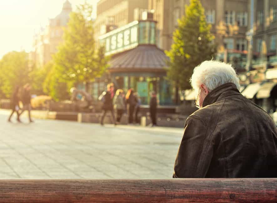 Back view of elderly man sat on public city center bench looking down