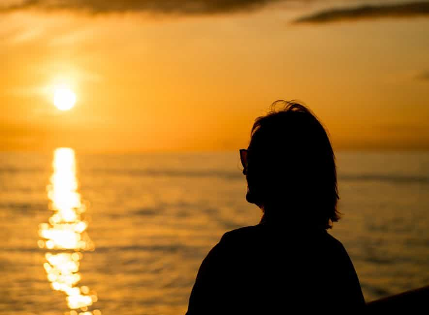 Silhouette photo of woman looking across calm sea at beautiful orange sunset