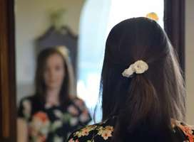 Head and shoulders back view of woman looking at mirror