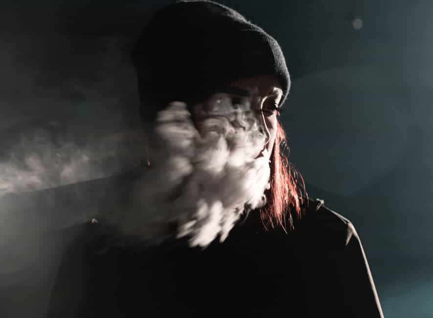 Portrait photography of person blowing smoke, most of face obscurred