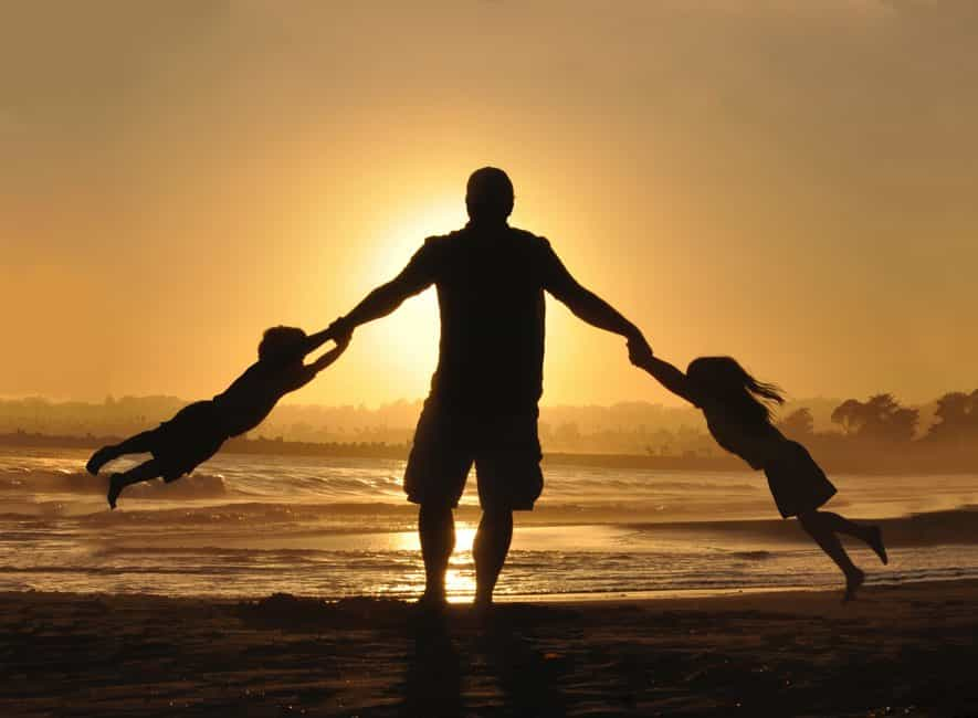 Silhouette of man holding his two children on shore during daytime