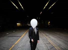Man in formal suit standing while holding white balloon obscuring face