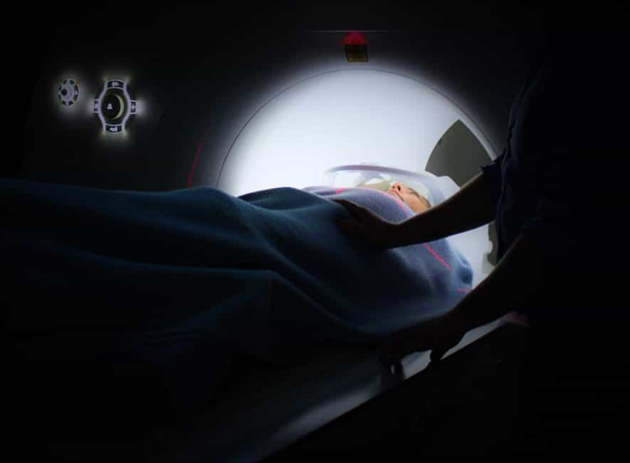 Person lying on ct-scan machine with reassuring hand from a nurse