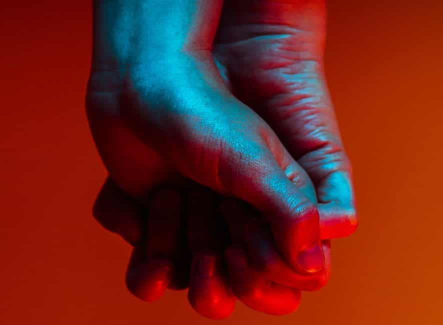 Two hands from two people clasped with deep red background