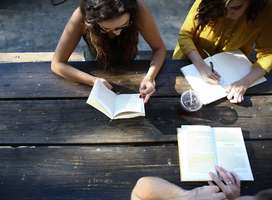 Students sat on outside desk reading, writing