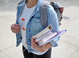Teen walking across college campus holding books, face obscurred