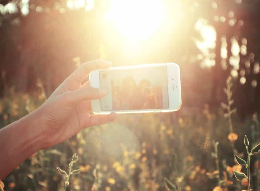 Taking selfie on smartphone in strong sunlight