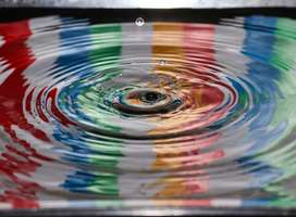 Time lapse photography of a water droplet ripple reflecting different colors