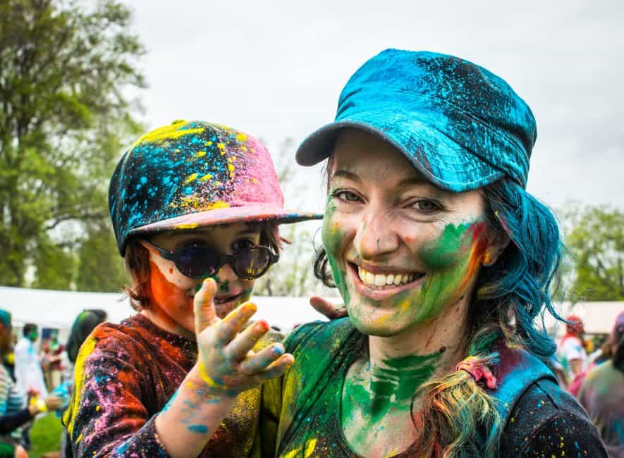 Mother and son smiling covered in different colored paints at public festival