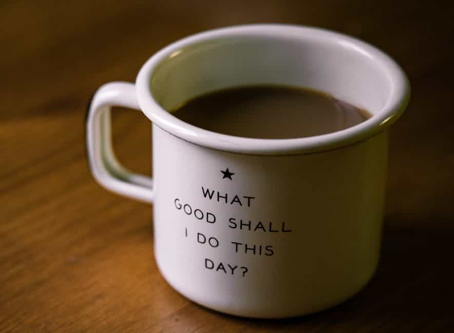 Mug of coffee with positive motivational message on side of cup